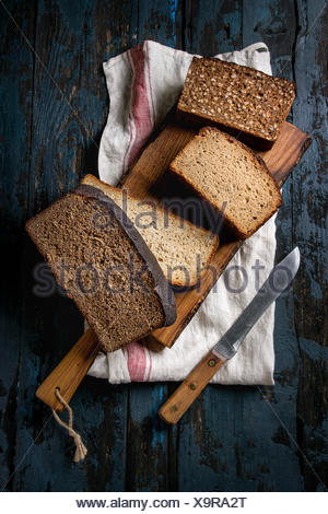 Variety loaves of sliced homemade rye bread whole grain and seeds on wooden cutting board with kitchen towel and knife over old dark wooden background - Stock Photo