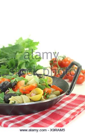Nudelpfanne mit Paprika, Rübstiel und Schinkenstreifen vor hellem Hintergrund - Stock Photo