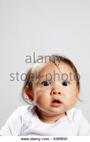 Portrait of baby girl looking surprised - Stock Photo