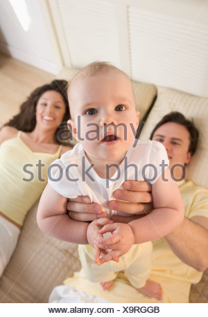 Infant held up by smiling couple - Stock Photo