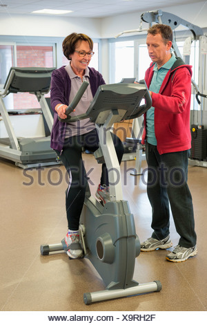 Trainer helping a woman with the cycle in a gym - Stock Photo