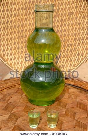 Green Lao Lao, bulbous glass bottle filled with alcohol, Laotian rice liquor, Phongsali, Phongsali province, Laos, Southeast As - Stock Photo