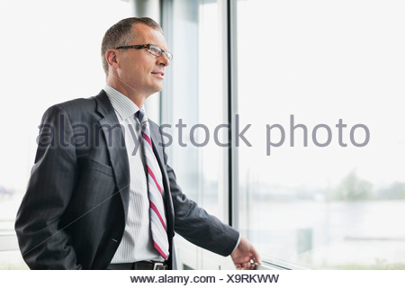 Thoughtful businessman looking out window in office - Stock Photo