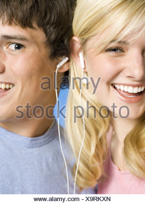 Portrait of a young couple with ear buds smiling - Stock Photo