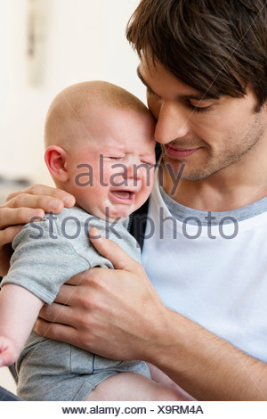 Father holding crying baby - Stock Photo
