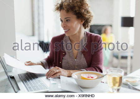 Woman paying bills online at home. - Stock Photo