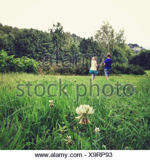 Boy and girl (10-11, 12-13) walking on meadow - Stock Photo