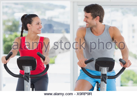 Couple working out at spinning class in bright gym - Stock Photo