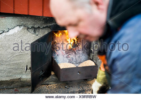Mature fisherman working at fireplace - Stock Photo