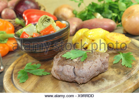 ostrich steak with baked potatoes and vegetables - Stock Photo