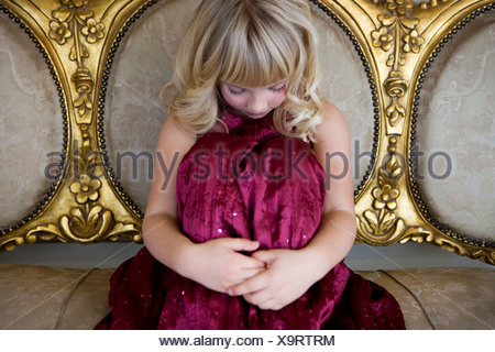 Young girl in a party dress crying or sulking - Stock Photo