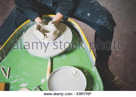 High angle view of young woman, waist down, sitting at pottery wheel making clay pot - Stock Photo
