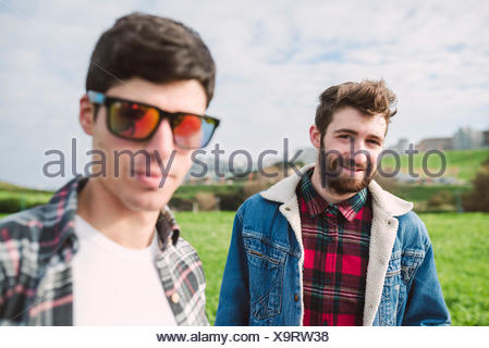 Portrait of smiling young man with his friend wearing mirrored sunglasses in the foreground - Stock Photo
