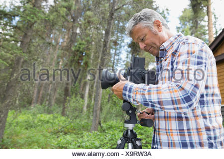 Man adjusting lens of SLR camera in yard - Stock Photo