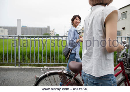 Two women walking along a footpath, pushing a bicycle. - Stock Photo