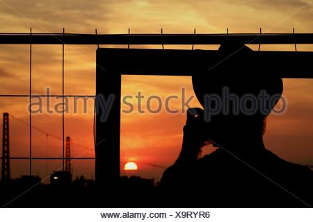 Rear View Of Silhouette Person Standing At Window Against Orange Sky During Sunset - Stock Photo