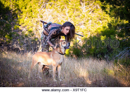 USA, Texas, Young woman standing with Blackmouth Cur dog - Stock Photo
