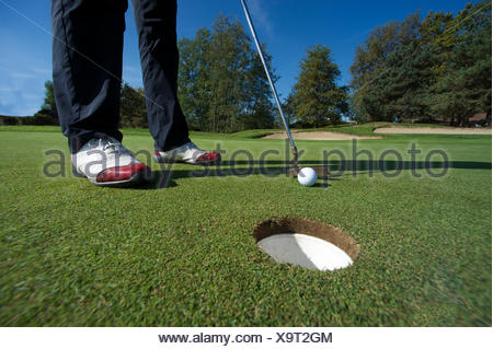 Close up of person putting golf ball on golf course - Stock Photo
