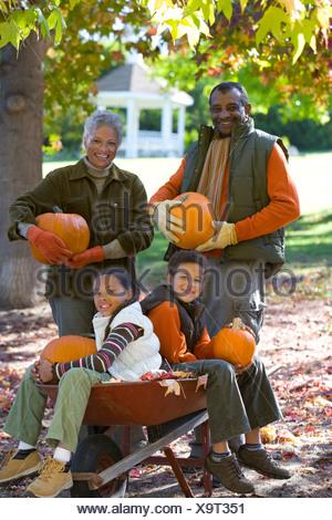 Grandparents and grandchildren holding pumpkins in autumn - Stock Photo