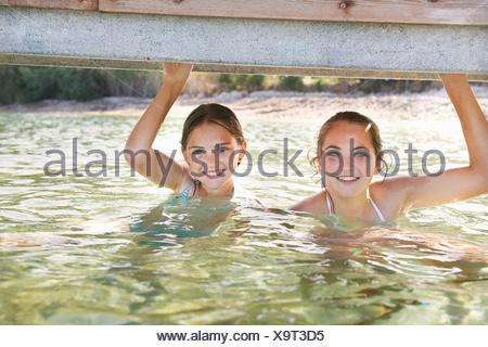 Portrait of two girls in sea holding onto pier - Stock Photo