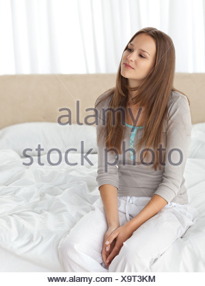 Thoughtful young woman sitting on the edge of her bed - Stock Photo
