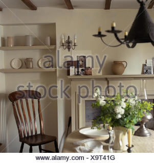 Antique wooden chair beside table set for lunch with a white cloth in a small cottage dining room with alcove shelving - Stock Photo
