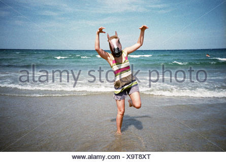 Man in horse head standing on beach - Stock Photo