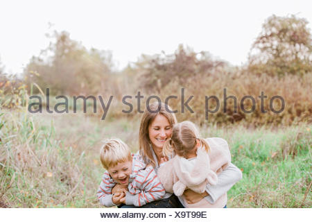 Mother and toddler children hugging in autumn park - Stock Photo