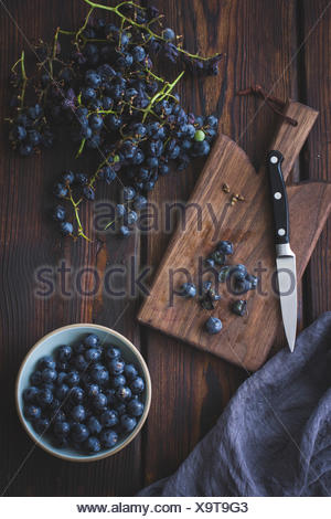 Black grapes on a chopping board - Stock Photo