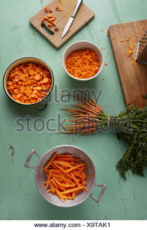 Chopped, sliced, grated and bunch of carrots on kitchen counter - Stock Photo