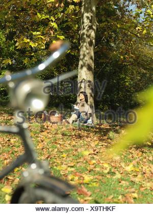 Woman with picnic under tree in Autumn - Stock Photo
