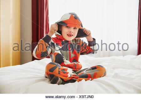 Young boy sitting on bed wearing hooded top - Stock Photo