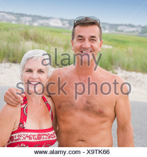 Portrait of a mature couple smiling with arm around - Stock Photo