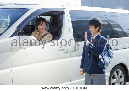 Junior High School Boy Talking to Mother in a Car - Stock Photo