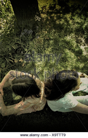 Two young girls sitting back to back under a tree - Stock Photo