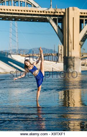 Dancer ankle deep in water, leg raised, balancing on one leg, in front of bridge, Los Angeles, California, USA - Stock Photo