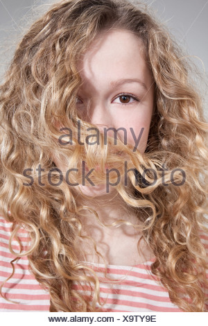 Teenage girl with hair covering face - Stock Photo
