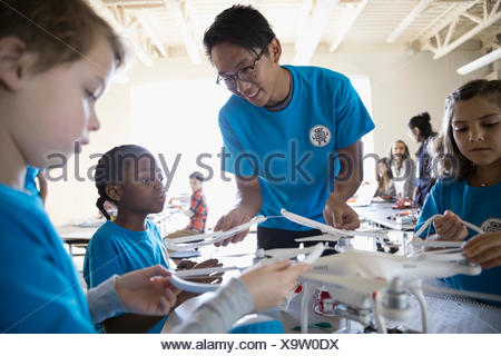 Male teacher helping pre-adolescent students assembling drone in classroom - Stock Photo