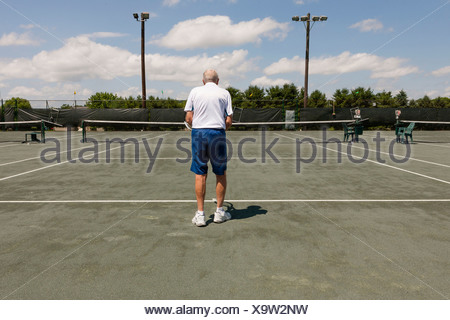 Rear view of senior man on tennis court - Stock Photo