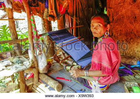 woman of the Palong tribe with traditional clothing works with a loom, Thailand, Chiang Rai - Stock Photo
