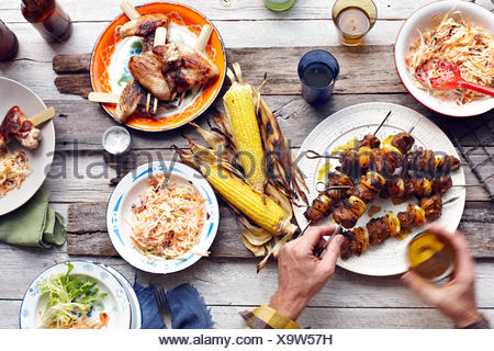 Mans hand picking up lamb and chicken skewer from table - Stock Photo