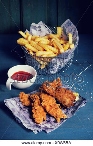 Chicken fries strips and legs on paper with basket of  French fries and bowl of ketchup sauce over blue wooden table. Turquoise - Stock Photo