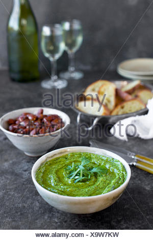 Arugula Chive Basil Pesto served in a ceramic bowl with crostini, almonds and wine.  Photographed fron front view on a black/brown background. - Stock Photo