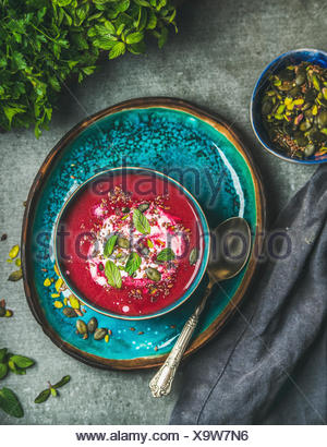 Spring detox beetroot soup with mint, chia, flax and pumpkin seeds on bright blue ceramic plate over grey concrete background, top view. Dieting, clea - Stock Photo