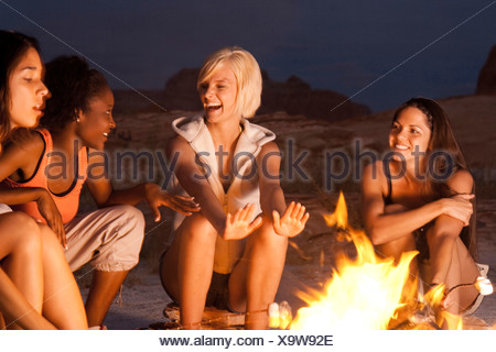 Women cooking marshmallows on campfire - Stock Photo