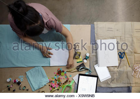 Overhead view female fashion designer cutting fabric in workshop - Stock Photo