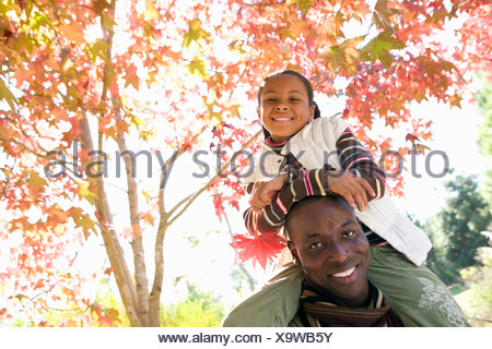 Father carrying daughter 7 9 on shoulders in autumn park girl holding red maple leaf smiling portrait tilt - Stock Photo
