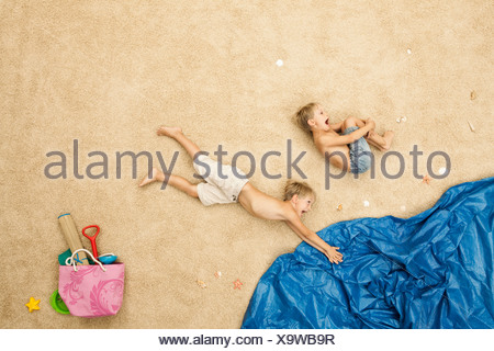 Germany, Boys jumping in water at beach - Stock Photo