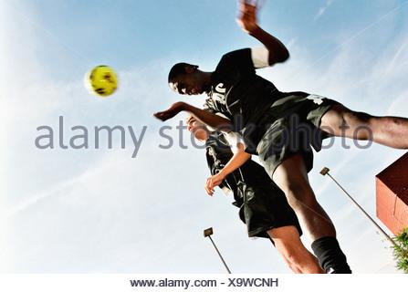 Footballers heading ball - Stock Photo