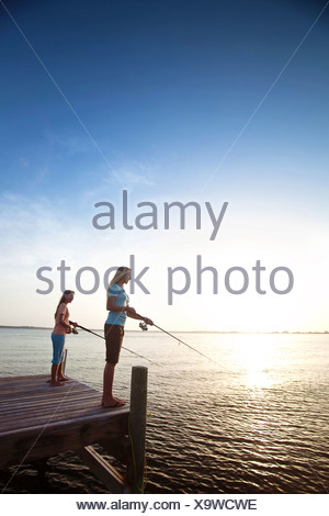 Two girls fish off a pier on the Santa Rosa Sound, Pensacola Beach, Florida at sunset. - Stock Photo